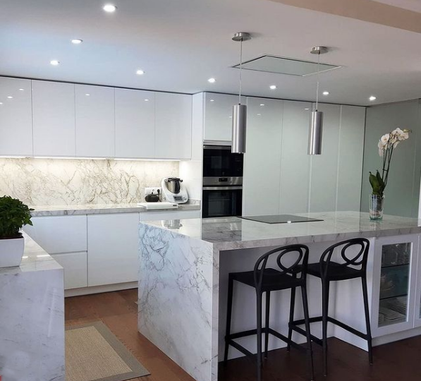 Una cocina moderna blanca con mármol.